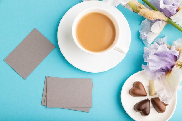 Szara wizytówka z filiżanką cioffee, czekoladowymi cukierkami i kwiatami tęczówki na niebieskiej pastelowej powierzchni