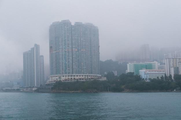 Szare betonowe wysokie drapacze chmur na wybrzeżu w mglistej pogodzie