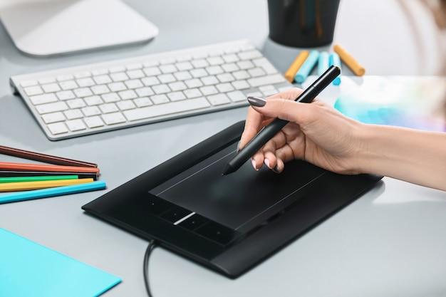 Szare biurko z laptopem, notatnik z pustym arkuszem, doniczka z kwiatkiem, rysik i tablet do retuszu