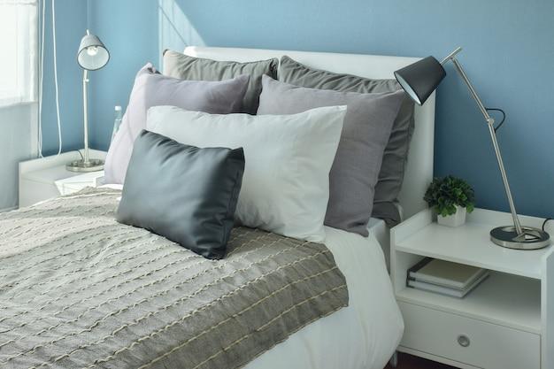 Szare, ciemnoszare i beżowe poduszki na łóżku z niebieską sypialnią na ścianie