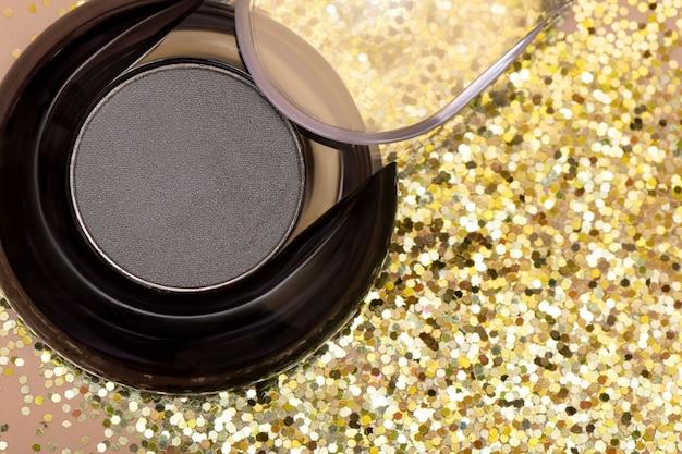 Szare cienie do makijażu na tle złotego brokatu.