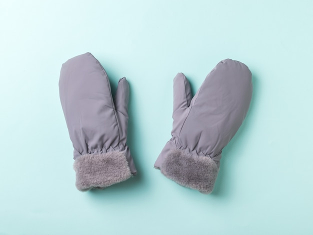 Szare ciepłe rękawiczki damskie na niebieskiej powierzchni. akcesoria do ochrony dłoni.