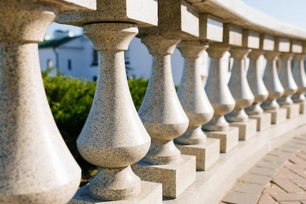 Szare granitowe tralki jako ogrodzenie w mieście