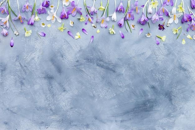 Szare i białe tło z teksturą z obramowaniem fioletowe i białe wiosenne kwiaty