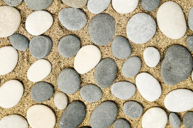 Szare i białe żwirowe kamienie na piasku podłogi. projektuj podłogę w ogrodzie ścieżkę lub ścianę na taras.