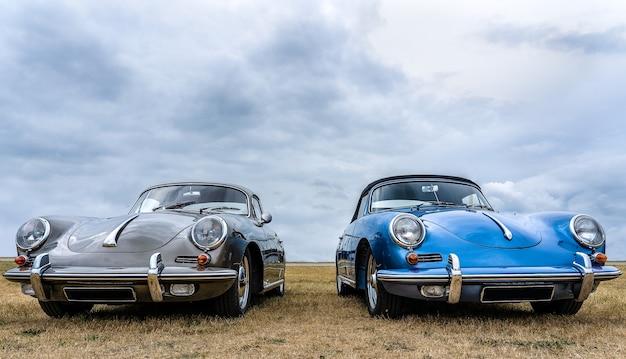 Szare i niebieskie samochody ustawione obok siebie pod zachmurzonym niebem