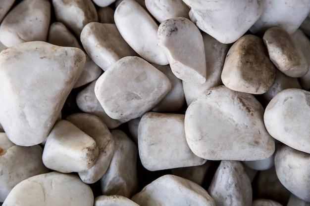 Szare kamienie o różnych kształtach w ogrodzie.