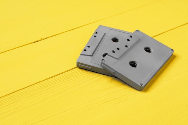 Szare kasety audio na żółtym tle widok z góry, kopia przestrzeń
