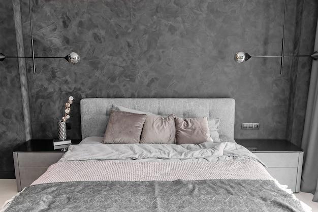 Szare łóżko w monochromatycznej sypialni z poduszkami i lampami na poddaszu na ścianie.