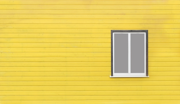 Szare okno na żółtej drewnianej ścianie