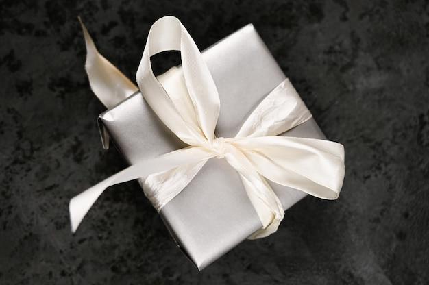 Szare opakowanie prezentowe z białą wstążką na tle czarnego marmuru