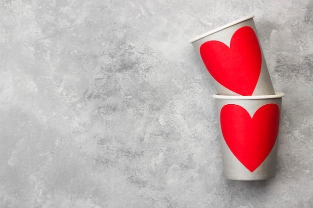 Szare papierowe kubki do napojów z czerwonym sercem na jasnym tle. widok z góry, miejsce.