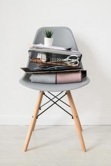 Szare plastikowe krzesło ze stosem materiałów biurowych lub rzeczy projektanta wnętrz z małą doniczką na górze stojącą w izolacji przy białej ścianie