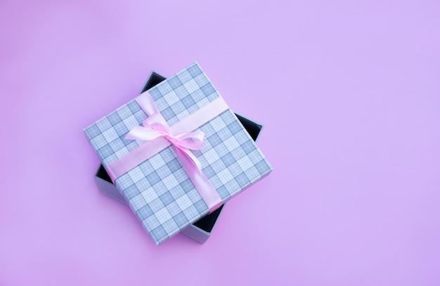 Szare pudełko w kratę z różową kokardką na różowym tle obraz z miejsca na kopię