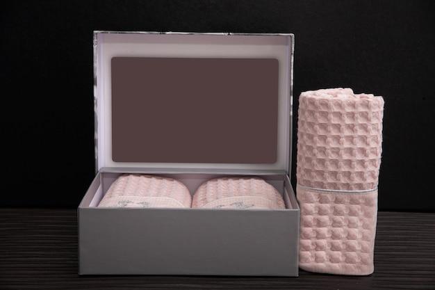 Szare pudełko z różowymi ręcznikami na ciemno.