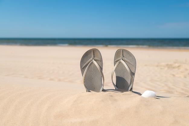Szare sandały na plaży w piękny słoneczny dzień.