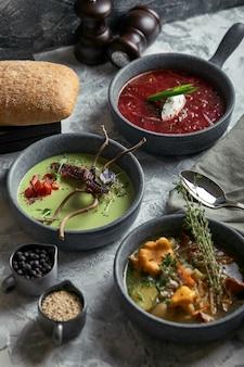 Szare talerze z różnymi zupami na szaro. talerz ze zupa szparagowa z ośmiornicą, talerz tradycyjnego barszczu z kwaśną śmietaną, talerz z zupą grzybową i stojący na wielobarwnym