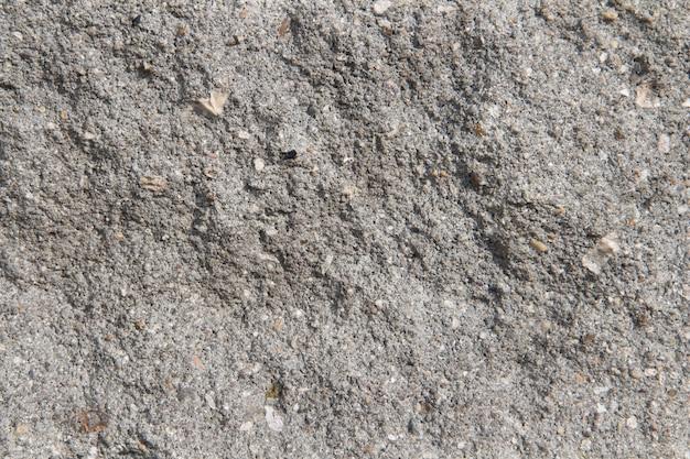 Szare tło betonu. pęknięty kamienny mur tło. beton z szarego reliefu.