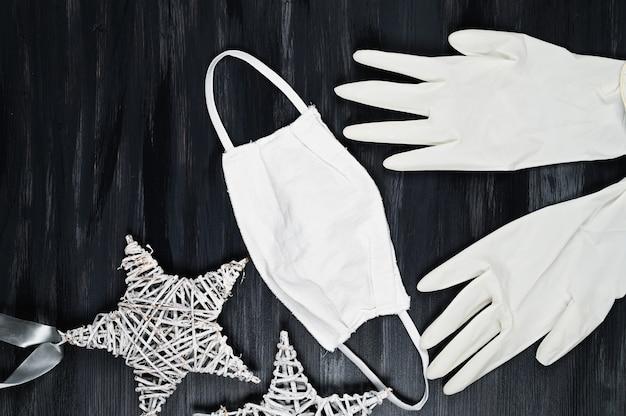 Szare tło boże narodzenie z białą maskę medyczną rękawice ochronne i drewniane gwiazdki