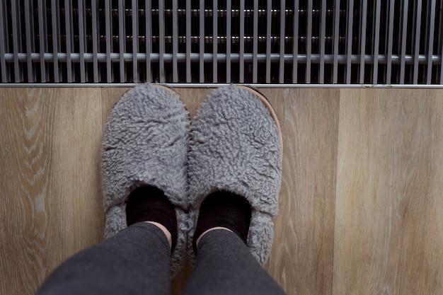 Szare trampki. zdjęcie stóp w szarych kapciach przy oknie. domowa atmosfera