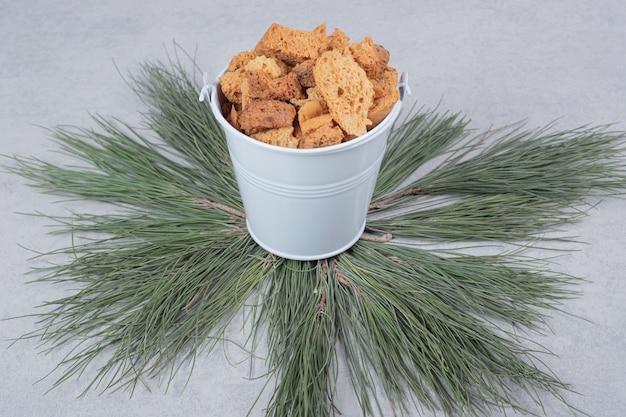 Szare wiadro pełne krakersów na zielonej gałęzi drzewa. wysokiej jakości zdjęcie