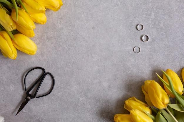 Szare z żółtymi kwiatami tulipany i stół nożyczki