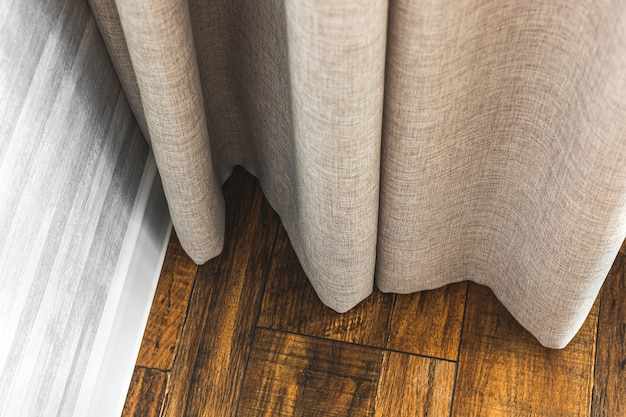 Szare zasłony w nowoczesnym wnętrzu mieszkania z drewnianą podłogą, koncepcja wystroju salonu w tle zdjęcie