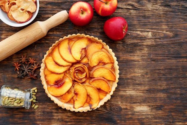 Szarlotka i czerwone jabłka na drewnianym stole z bliska