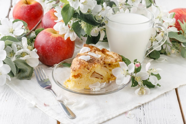 Szarlotka klasyczny amerykański deser. domowe pieczenie na drewnianym stole. czerwone jabłka przy torcie