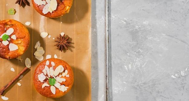 Szarlotka lub babeczki cynamonowe z jabłkami i płatkami migdałów ozdobione liśćmi mięty, układ na szarym stole z miejscem na tekst. makieta do pieczenia domowej roboty, widok z góry babeczki