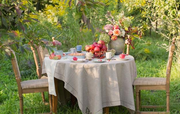 Szarlotka na nakrytym stole w ogrodzie w słoneczny dzień