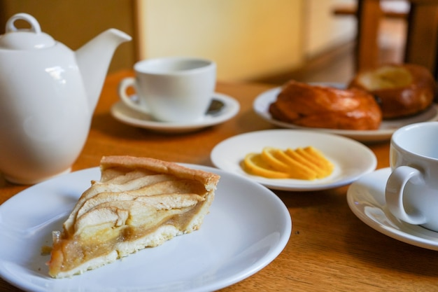Szarlotka z herbatą i cytryną na stole