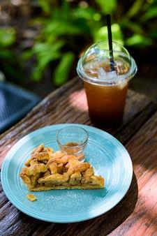 Szarlotka z kawą na drewnianym stole w ogrodzie