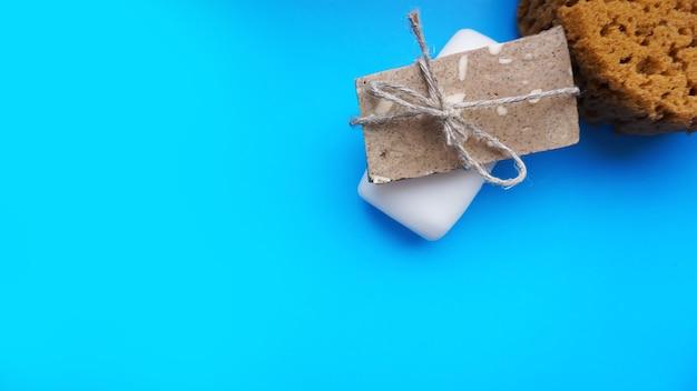 Szaro-białe mydło ręcznie robione owinięte sznurkiem na niebieskim czystym tle