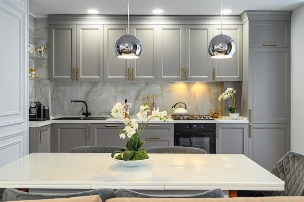 Szaro-białe współczesne klasyczne wnętrze kuchni ze stołem jadalnym zaprojektowanym w nowoczesnym stylu, widok z przodu