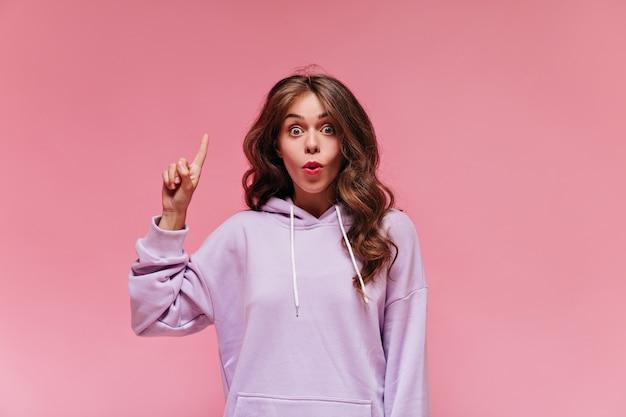 Szarooka brunetka w fioletowym sportowym stroju wskazuje na miejsce na tekst na białym tle