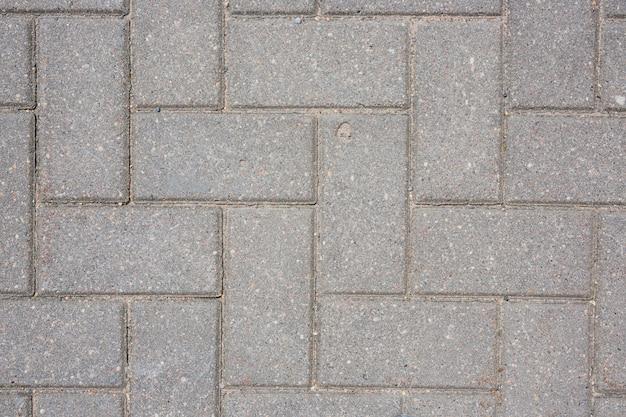 Szarości betonowa płytka na zmielonym bruk ścieżki tekstury tle