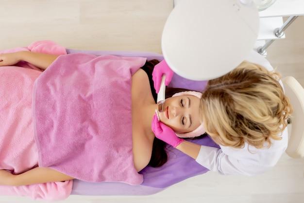 Szarpanie ultradźwiękowe. młoda kobieta odbiera oczyszczanie twarzy peeling kawitacyjny ultradźwiękami. kosmetyka oczyszczająca pielęgnacja skóry twarzy. ręce kosmetyczki przy pracy, czyszczenie skóry strumieniem wody.