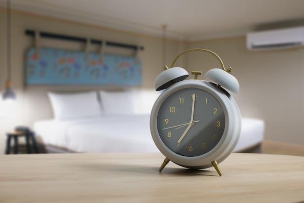 Szary budzik na drewnianym stole w sypialni