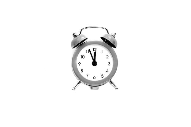 Szary budzik vintage pokazuje godzinę 12 na białym tle. obudź się i pospiesz się. gorąca wyprzedaż, ostateczna cena, ostatnia szansa. odliczanie do północy nowego roku.