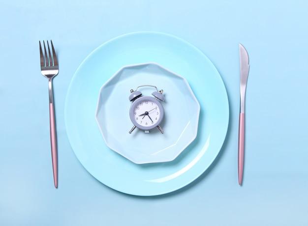 Szary budzik, widelec i nóż w pustym niebieskim talerzu na niebiesko. pojęcie przerywany post, pora lunchu, dieta i utrata masy ciała. widok z góry, płaskie układanie, minimalizm.