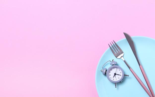 Szary budzik, widelec i nóż w pustym niebieskim talerzu na różowo. pojęcie przerywany post, pora lunchu, dieta i utrata masy ciała. widok z góry, leżał płasko, minimalizm.