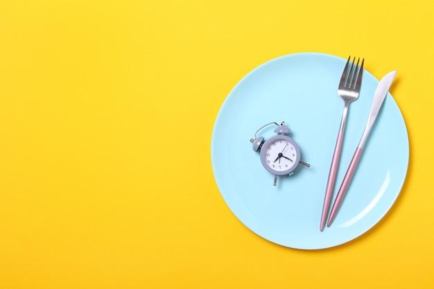 Szary budzik, widelec i nóż w pustym niebieskim talerzu na żółtym. pojęcie przerywany post, pora lunchu, dieta i utrata masy ciała. widok z góry, płaskie układanie, minimalizm.