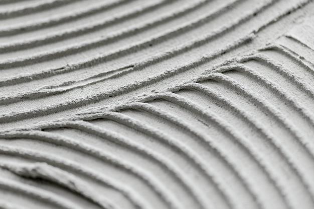Szary falisty wzorzysty beton teksturowany tło