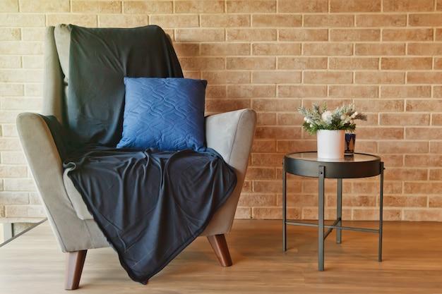 Szary fotel ze stołem we wnętrzu salonu o ścianę z cegły. przytulny obszar z sofą z niebieskim kocem i poduszką. na stole wazon z zielonymi kwiatami. koncepcja tła wnętrz. skopiuj miejsce