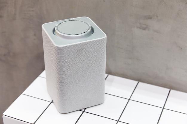 Szary głośnik bluetooth, kwadrat, kolumna muzyczna stoi na kafelku białych kwadratów