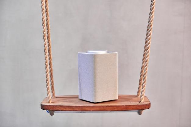Szary głośnik bluetooth, kwadratowa kolumna muzyczna stoi na kafelku białych kwadratów