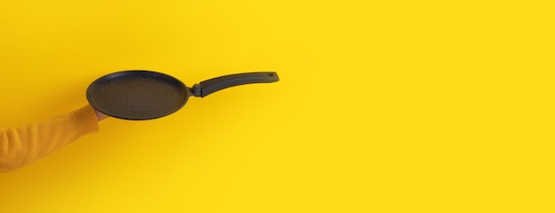Szary granitowy wafel i patelnia do pieczenia naleśników w ręku na żółtym tle, panoramiczna makieta z miejscem na tekst