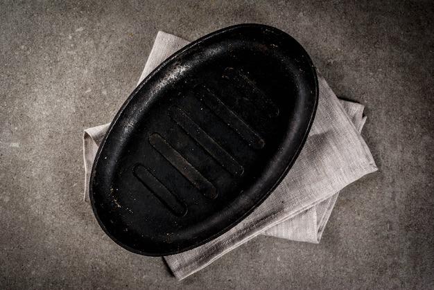 Szary kamień kulinarne tło z pustej czarnej patelni