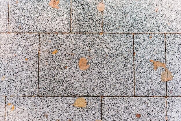 Szary kamienny bruk tekstura. kostka brukowa z żółtymi jesiennymi liśćmi